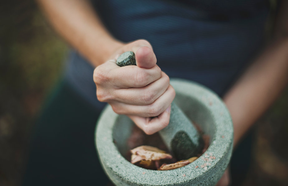 A person grinding leaves in a mortar with a pestle