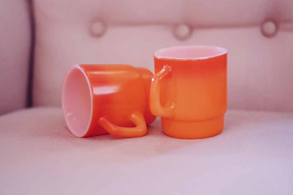 two orange mugs on a couch