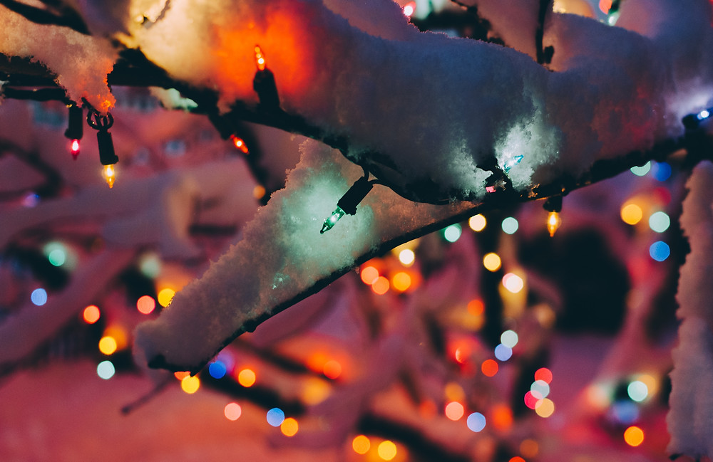 Christmas lights glowing on a snow covered branch