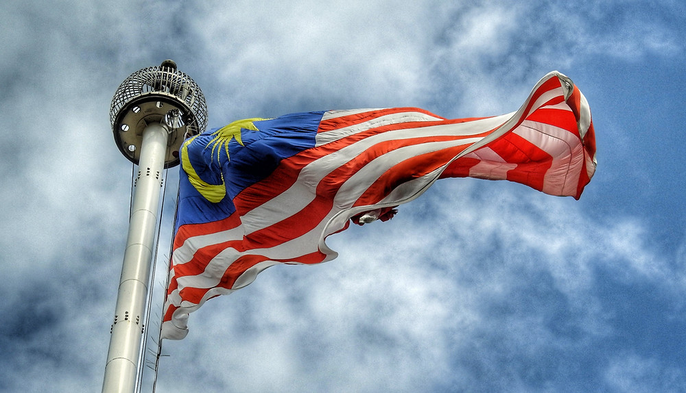 Photograph of Malaysian flag flying in wind amongst blue sky
