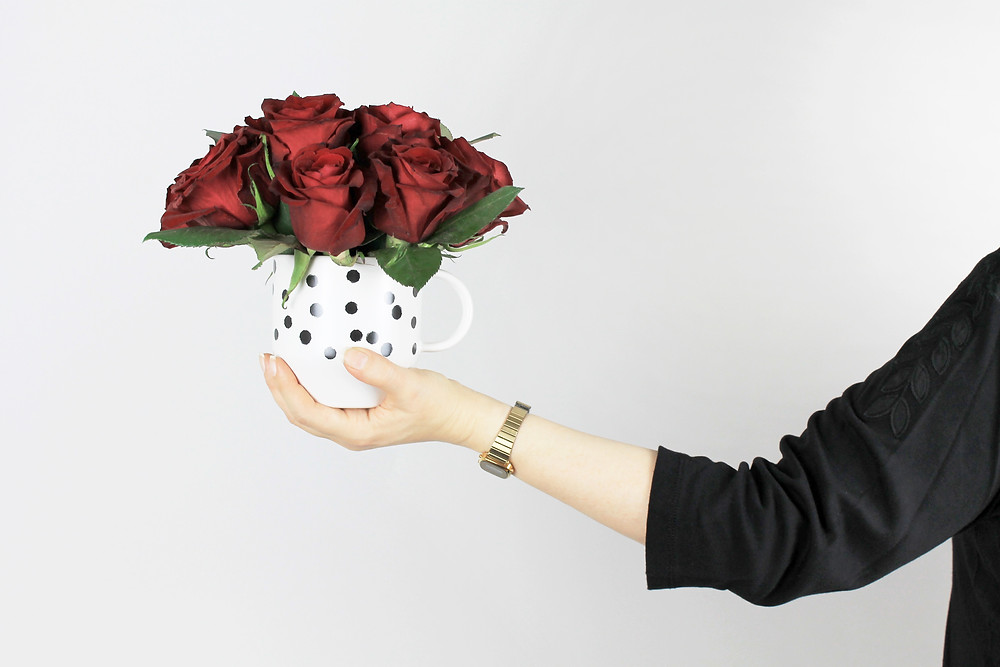 A woman holding a polka dot vase filled with red roses