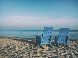 Image by Aaron Burden. Two chairs on the beach, facing the ocean