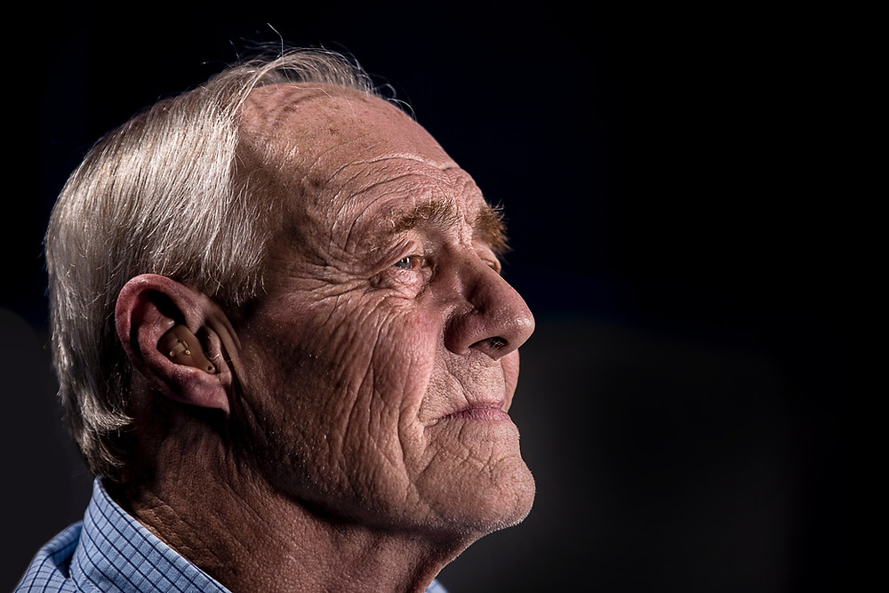 old man looks worried   older American facing death   gray haired man with sad eyes   hearing aid fits older man's ear   10 worries of older Americans