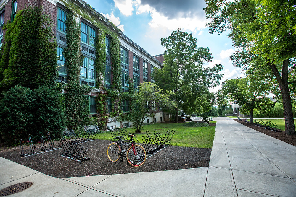 Picture of school building with one bicycle at the bike rack.