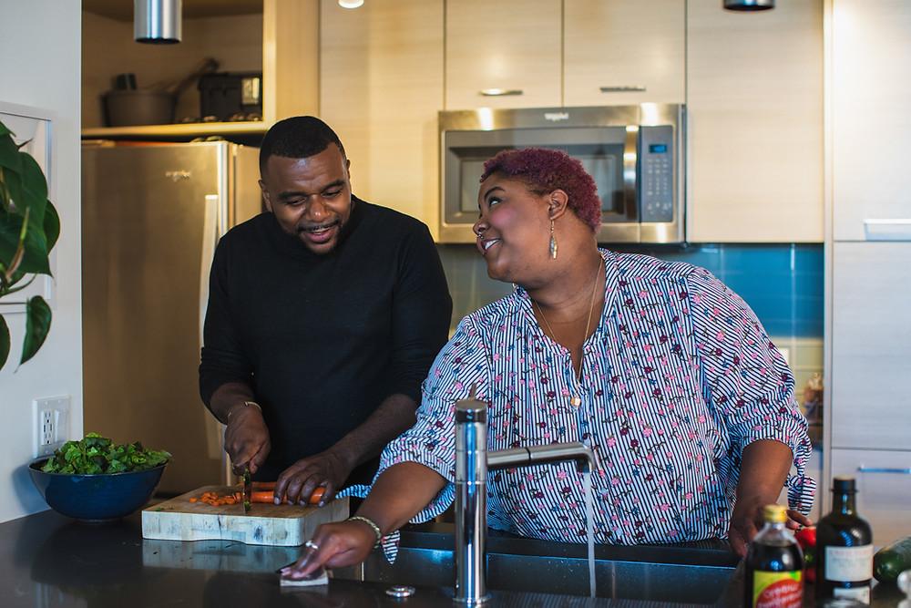Casal em frente à pia da cozinha, preparando uma refeição. Homem e mulher estão lado a lado; ele corta legumes e ela limpa a pia. Os dois se olham.