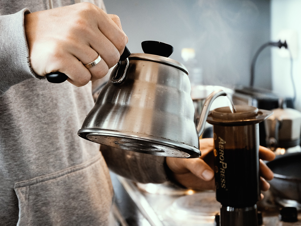 Person pouring hot water from a goose neck kettle to an Aeropress.