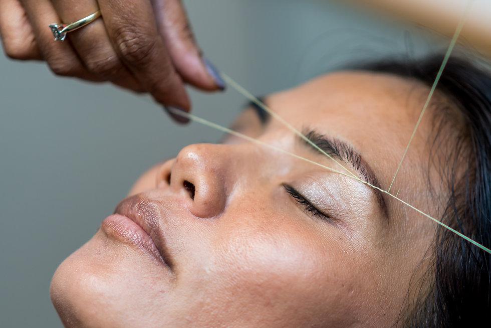 A woman has her eyebrows threaded.