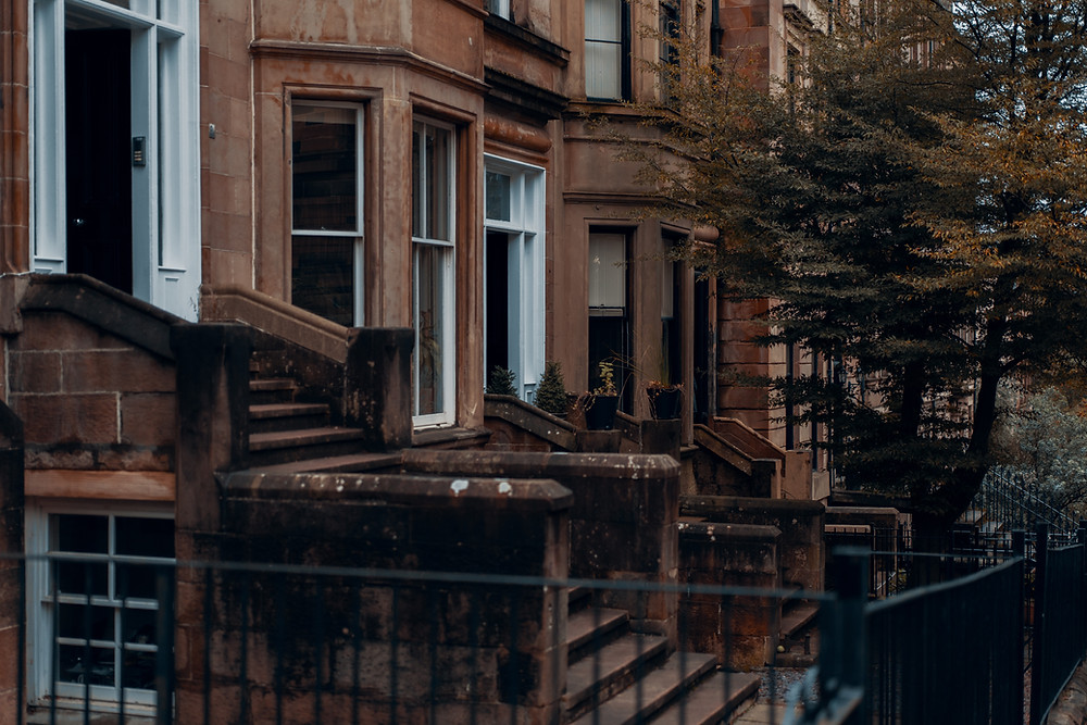 Brown sandstone tenements with steps leading up to the door and railings outside