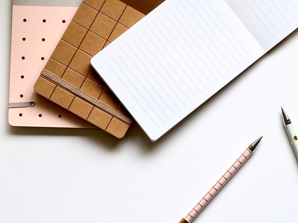 orderly writing implements such as journals and pens laid out on a plain background