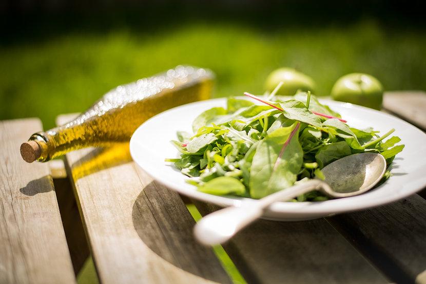 Une salade dans une assiette avec des couvert avec une bouteille en verre jeune à côté, fermée parun bouchon en liège. Tout cela est déposé sur une table en bois