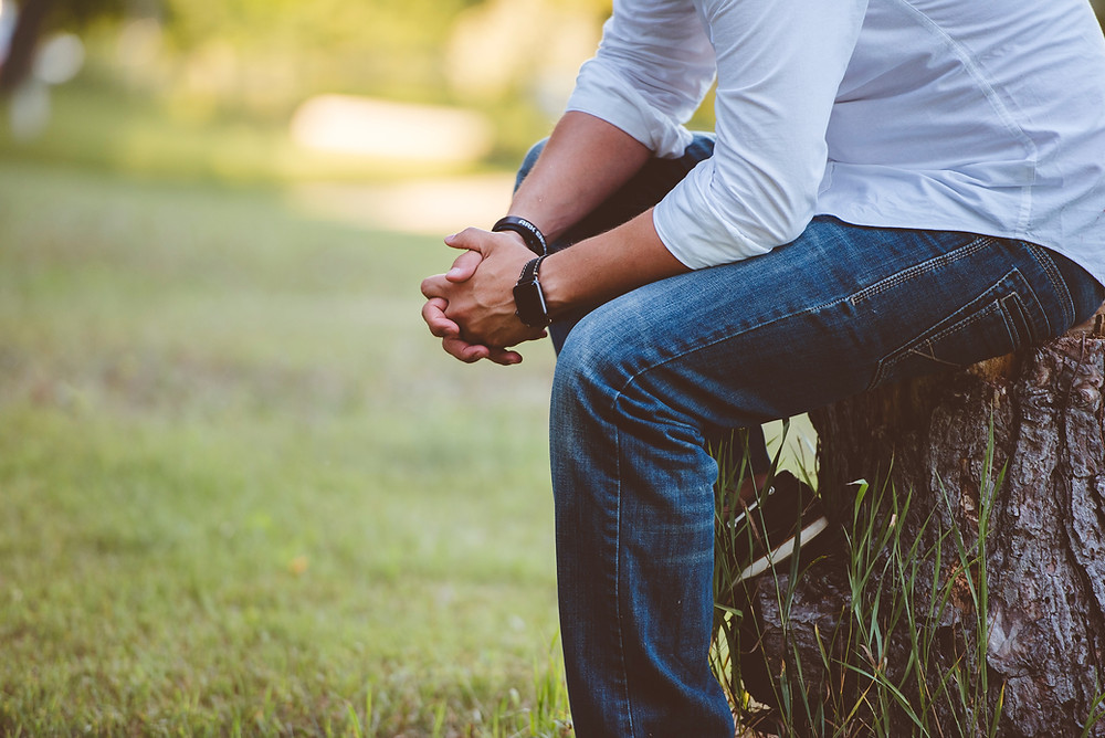 Man sitting on tree stump leaning forward with hands folded