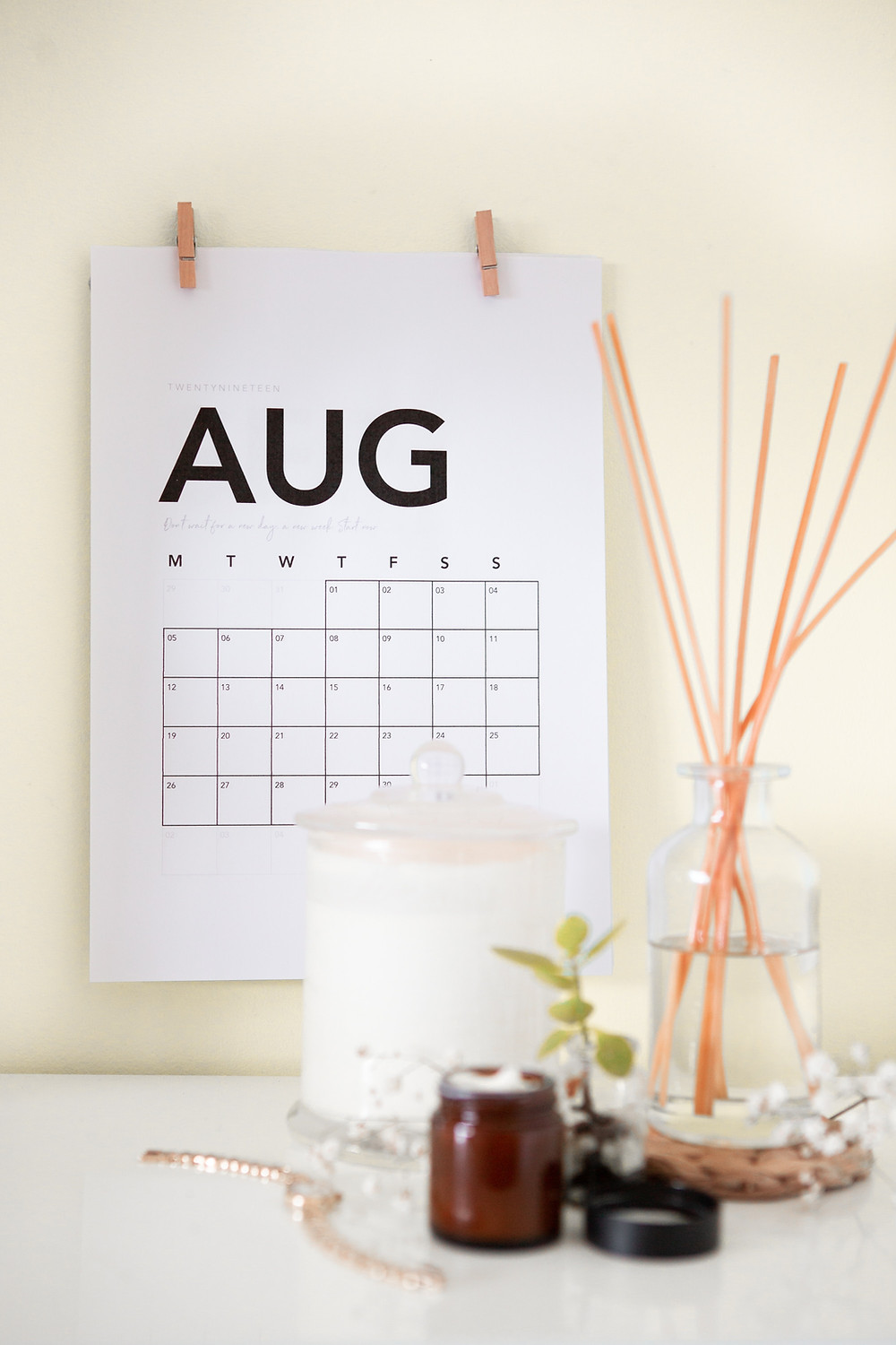 wall calendar turned to August with incense and candle in foreground