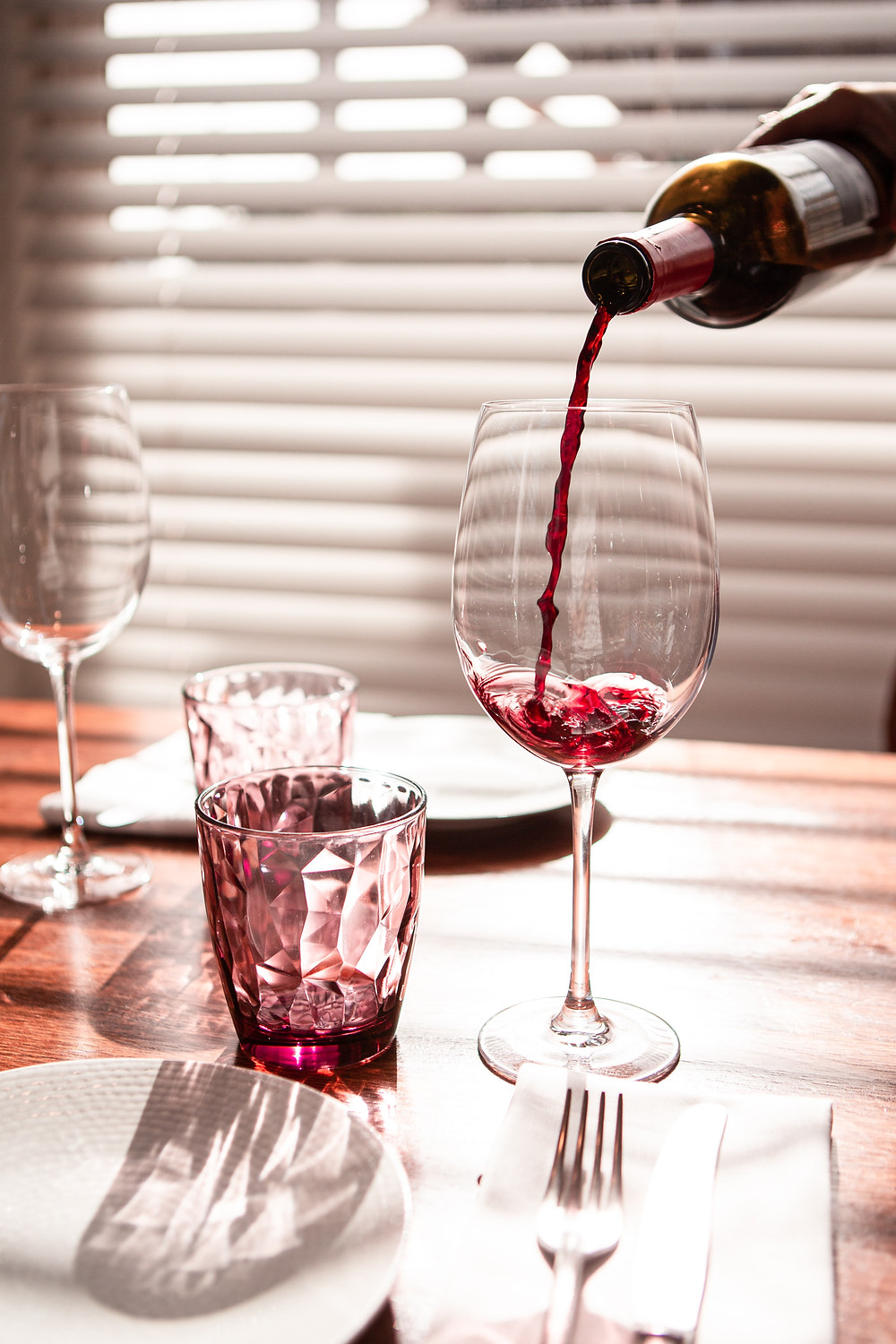a table set for dinner, a hand is pouring red wine from a bottle into a large red wine glass
