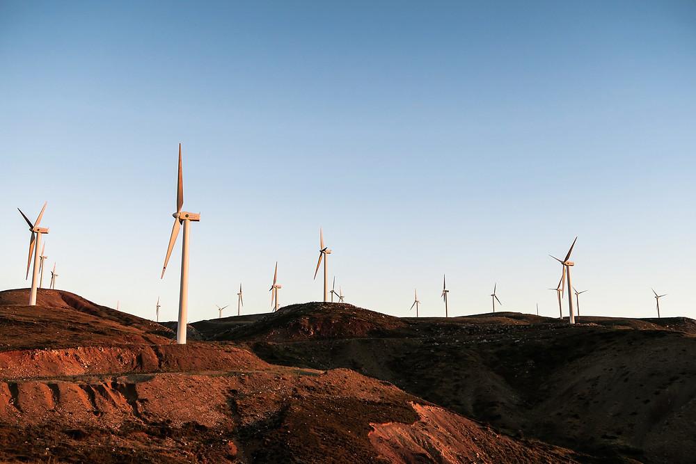 A windmill farm on red hills.