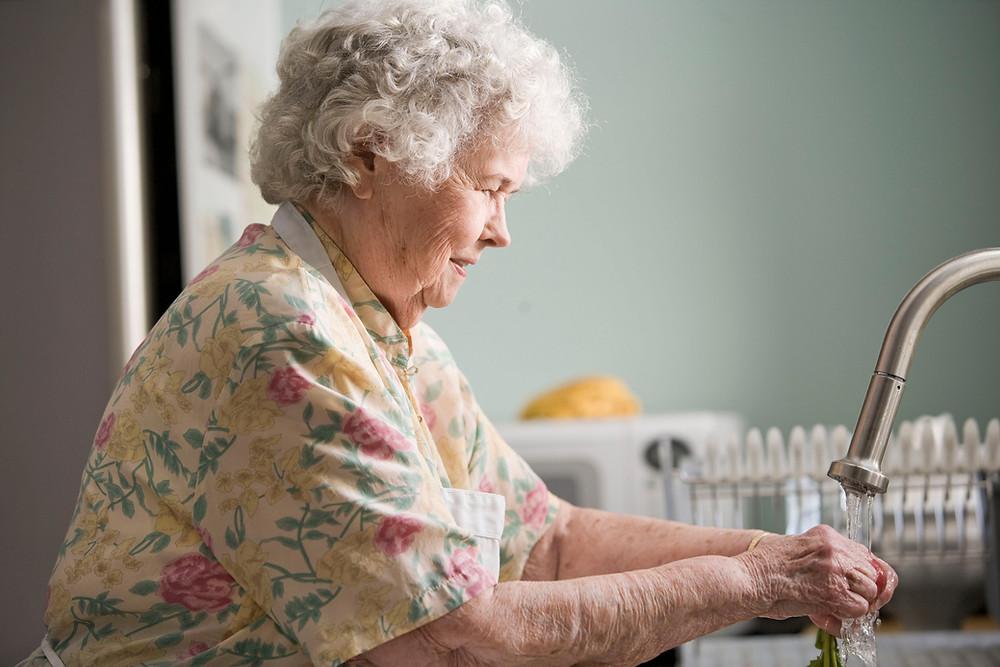 Elderly women washing dishes.