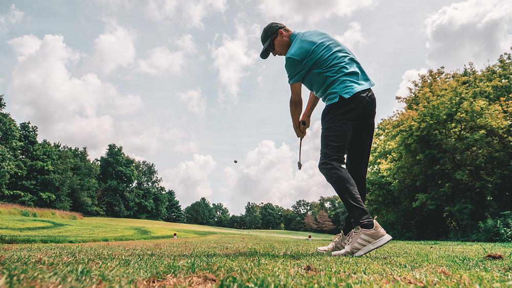 A golfer swinging his golfclub through the golfball