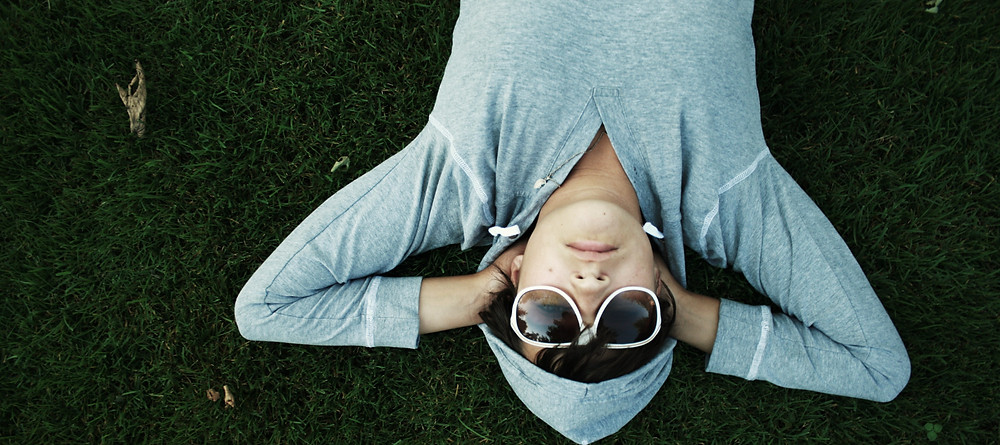 [A stock image of a person lying in the grass upside down wearign sunglasses]