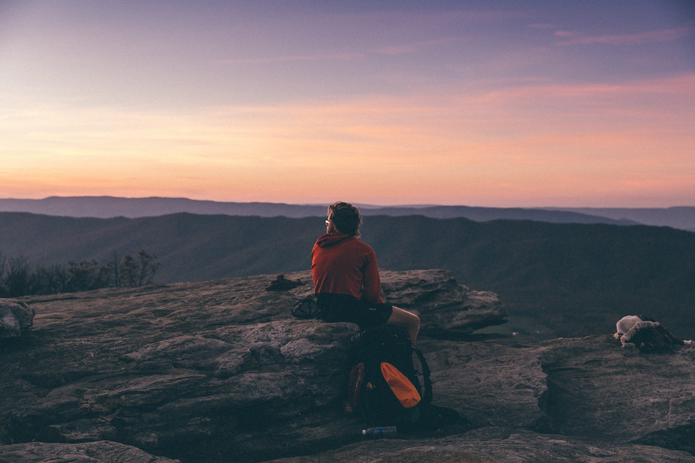 young male hiker sitting on rock and looking out at mountains at twilight