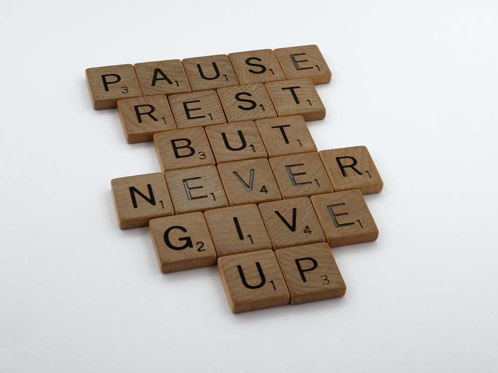 letter tiles spelling out Pause, Rest, But, Never, Give, Up