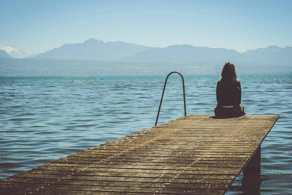 A woman sitting on the edge of a pier on a lake with mountains in the background