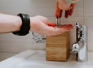 Person Washing Hands in Public Bathroom