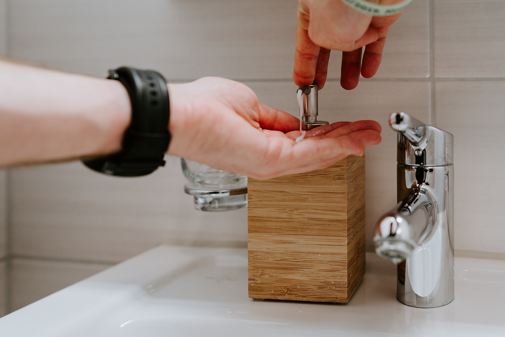 A person is reaching to pump some liquid out of a bamboo soap dispenser. It sits next to a silver tap suggesting they are going to wash their hands