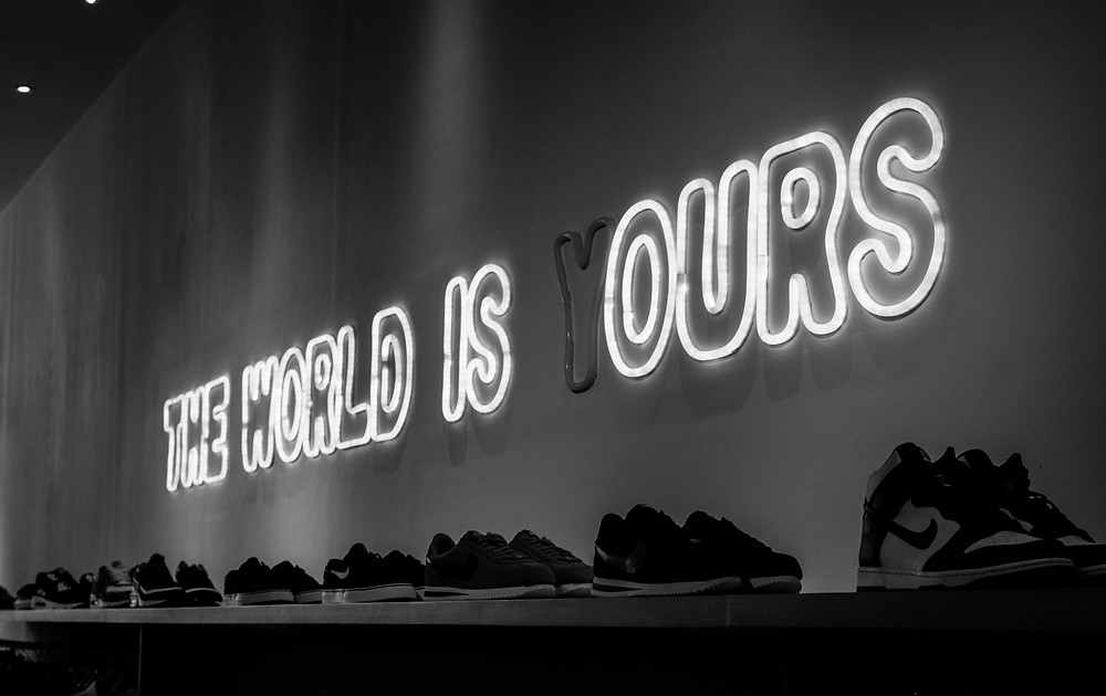 A display of nike shoes with a neon sign above it saying 'the world is (y) ours'