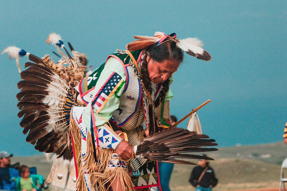A Native American dancing in Ceremonial wardrobe.