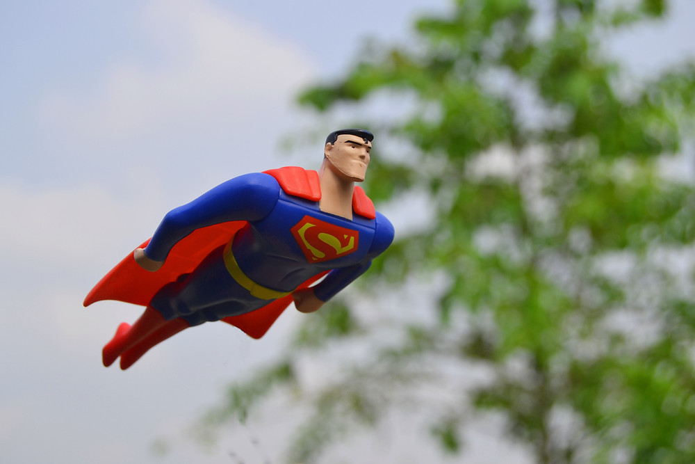 A plastic toy of comic book hero, Superman in flight in mid air
