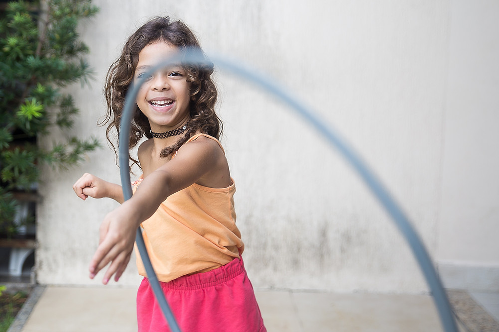 Girl with brown hair spinning a hula hoop around her arm.