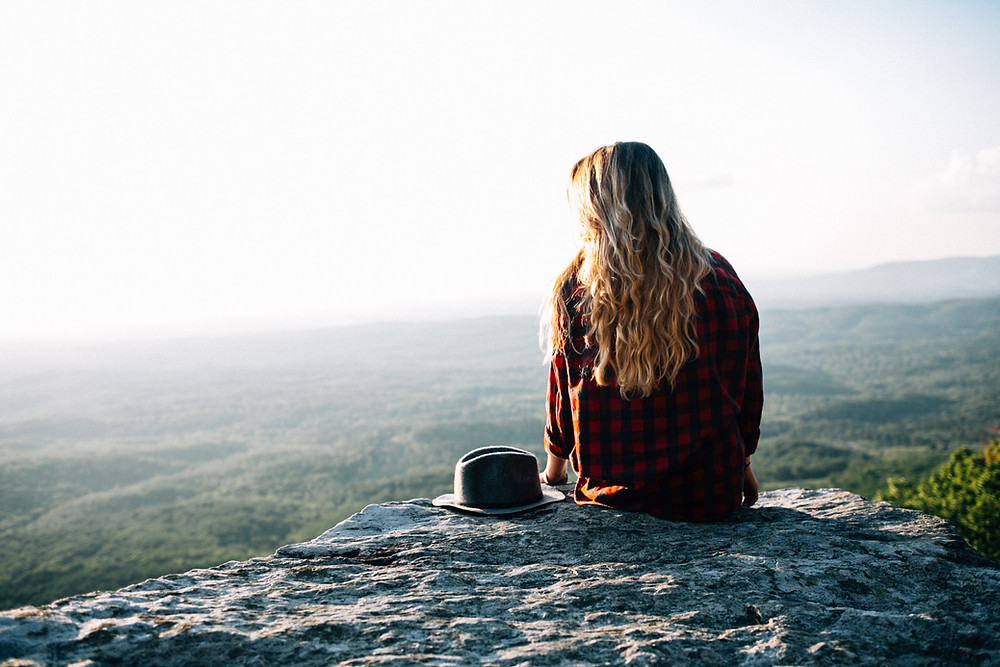 Girl sitting on edge of cliff facing valley below