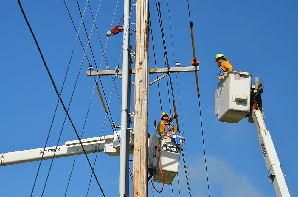electricians in buckets fixing power lines