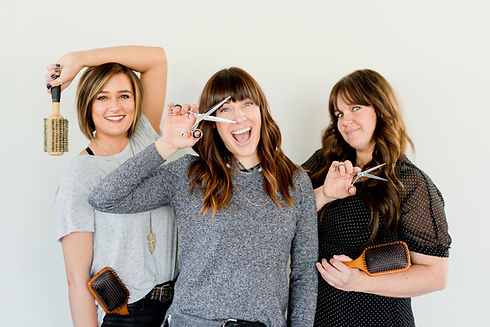 hairstylists posing with hair tools