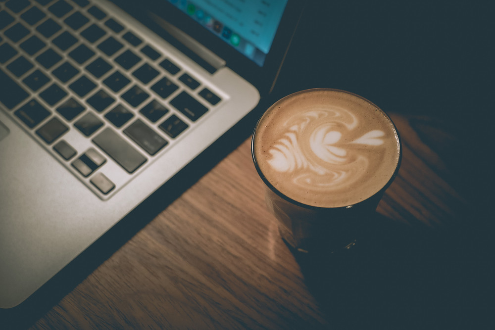 A cup of coffee with latte art beside a laptop computer