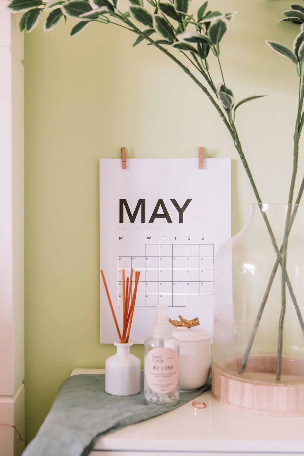 Wall calendar showing the month of May with some decorative candles and plants