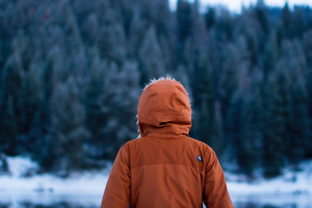 Person bundled up outside looking at snow covered pond during winter