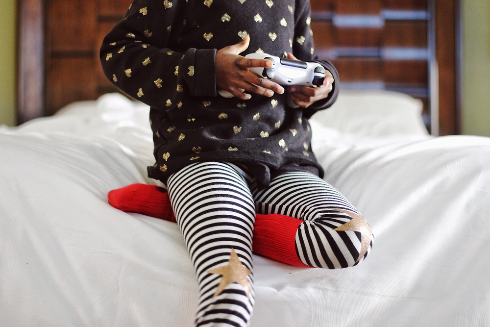 five year old child playing with a video game console