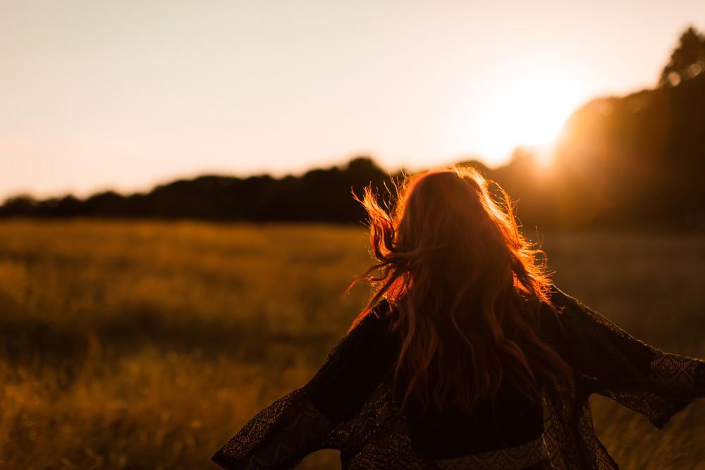 woman running through golden fields with sun rising