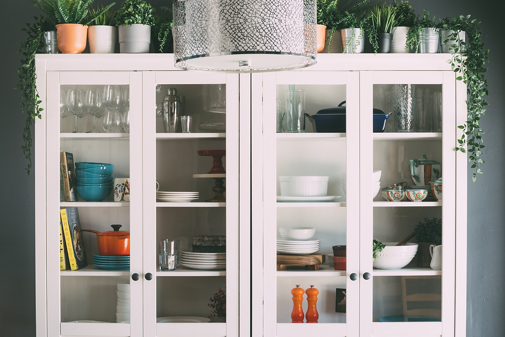 White storage unit with bowls, plates, and glasses inside