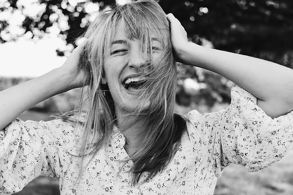 Image by Hannah Gullixson - Woman with blonde hair blowing in her face laughing with her hands on her head with her eyes closed