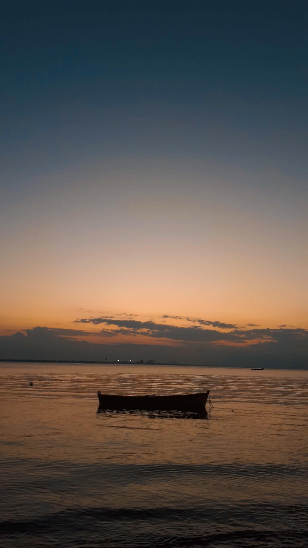Paisagem ao pôr do sol. Na parte debaixo da imagem, o mar e, bem no centro, um pequeno barco, em formato de jangada. Na parte superior, o céu em tons alaranjados e azuis, com algumas nuvens no horizonte e, acima, totalmente limpo.