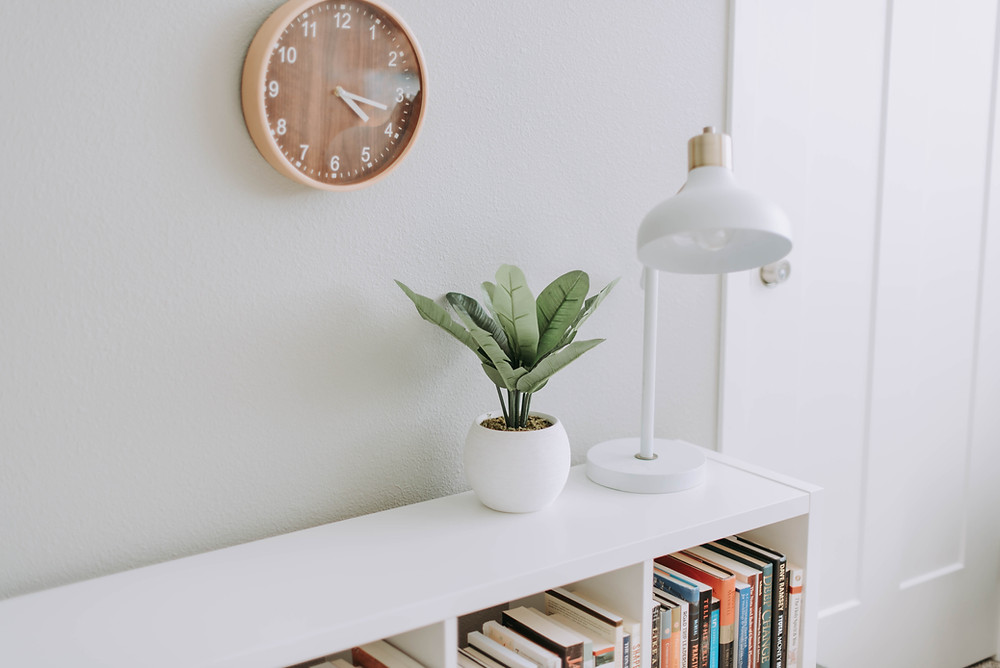 White bookcase with a small plant and clock on the wall
