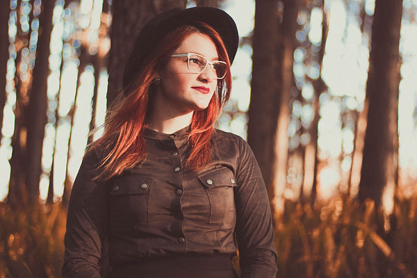 Image by Allef Vinicius - Woman in glasses and hat starring off into the distance.