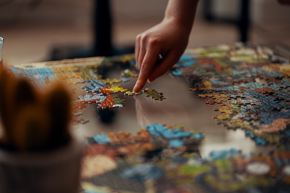 A jigsaw puzzle is being put together on a table. A person celebrating National Puzzle Day January 29