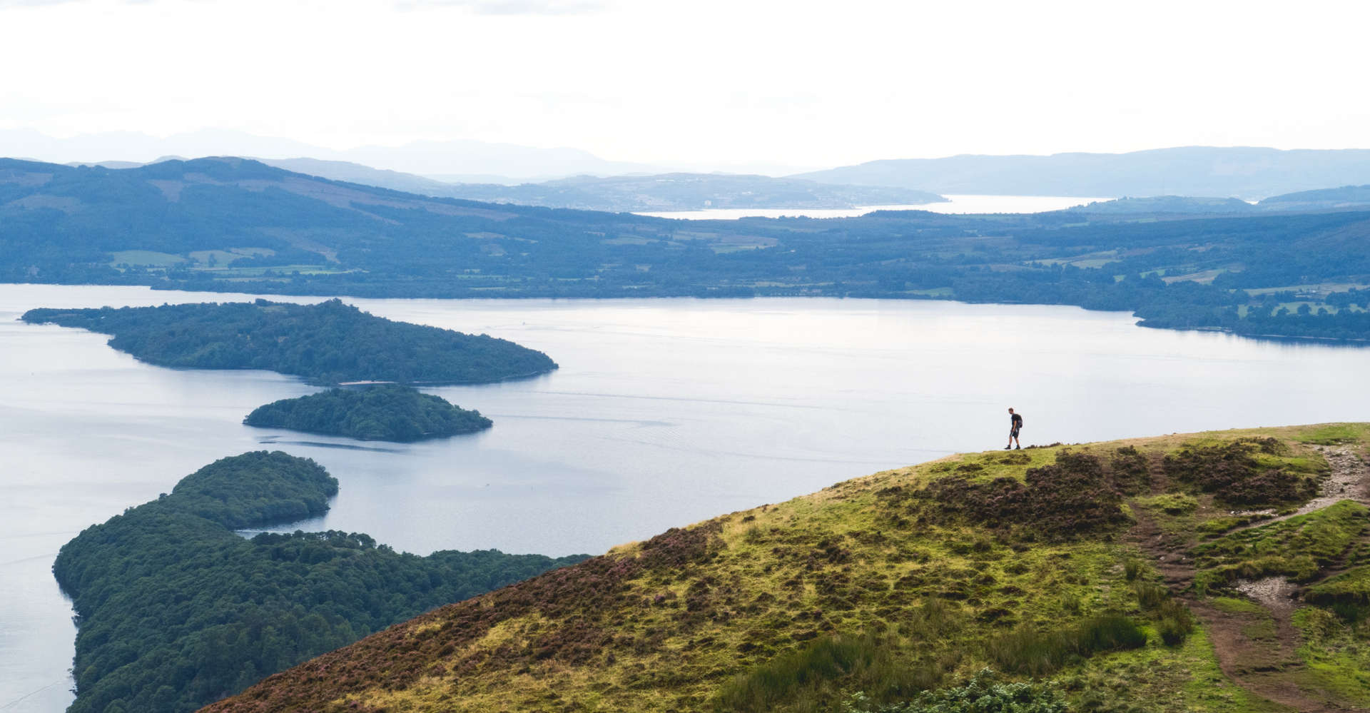 man on private tour looking at islands of loch lomond in scotland