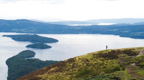 man walking on hills looking over loch lomond and islands