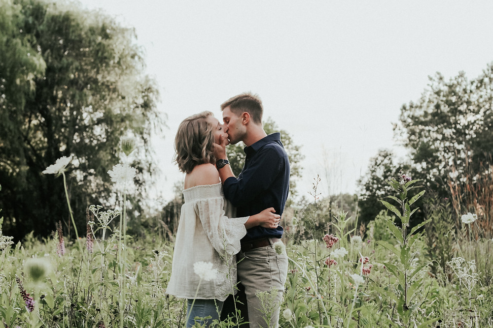 Couple kissing in a field of flowers