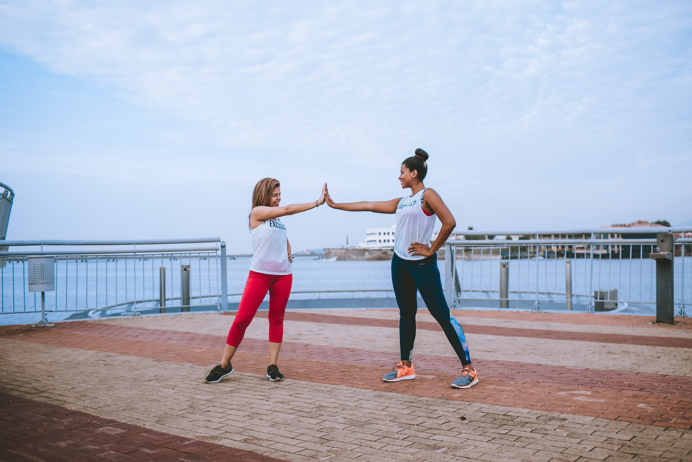 women high five each other during workout