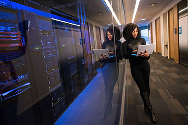 woman leaning up against servers with laptop
