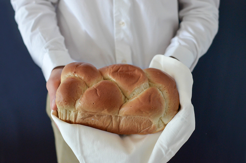 person in white shirt holding freshly baked bread in a white linen towel